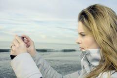 Mujer que toma cuadros con smartphone Foto de archivo