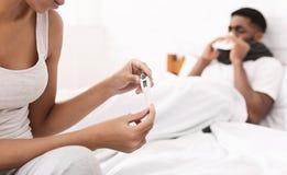 Mujer que toma cuidado del hombre enfermo con la fiebre que miente en cama imagenes de archivo