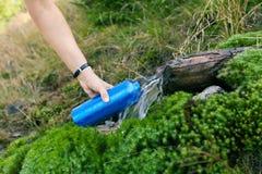 Mujer que toma el agua a partir del resorte fotos de archivo libres de regalías