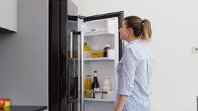 Mujer que toma el envase de comida del refrigerador en la cocina almacen de video