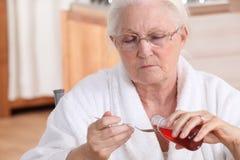Mujer que toma el jarabe de la tos Fotografía de archivo libre de regalías