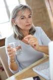 Mujer que toma el medicamento con la ayuda de Internet foto de archivo