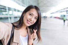 Mujer que toma el selfie con gesto coreano del finger del corazón del estilo Foto de archivo libre de regalías