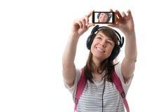 Mujer que toma el selfie con la cámara del smartphone y t que escucha Imagenes de archivo