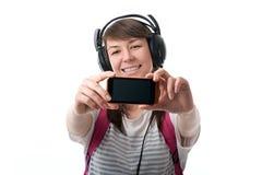 Mujer que toma el selfie con la cámara del smartphone y t que escucha Fotografía de archivo