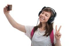 Mujer que toma el selfie con la cámara del smartphone y t que escucha Foto de archivo