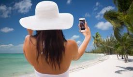 Mujer que toma el selfie con smartphone en la playa Imágenes de archivo libres de regalías