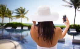 Mujer que toma el selfie con smartphone en la playa Imagen de archivo libre de regalías