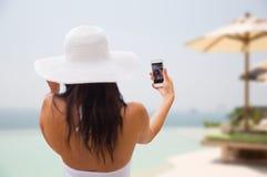 Mujer que toma el selfie con smartphone en la playa Foto de archivo
