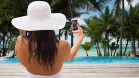 Mujer que toma el selfie con smartphone en la playa Imagen de archivo