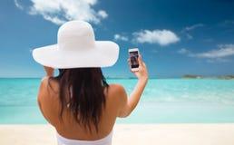 Mujer que toma el selfie con smartphone en la playa Imagenes de archivo