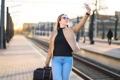 Mujer que toma el selfie con el teléfono móvil en plataforma del tren Fotografía de archivo libre de regalías