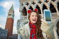 Mujer que toma el selfie de la Navidad y que muestra la victoria en Venecia Imagen de archivo libre de regalías