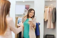 Mujer que toma el selfie del espejo por smartphone en la tienda Fotos de archivo libres de regalías