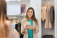 Mujer que toma el selfie del espejo por smartphone en la tienda Imagen de archivo libre de regalías