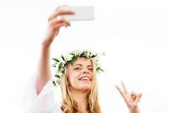 Mujer que toma el selfie del smartphone y que muestra paz Fotos de archivo libres de regalías