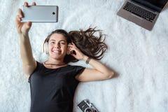 Mujer que toma el selfie en cama, música Imagen de archivo libre de regalías