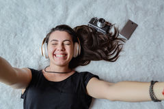 Mujer que toma el selfie en cama, música Fotos de archivo libres de regalías