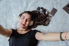 Mujer que toma el selfie en cama, música Fotografía de archivo