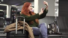 Mujer que toma el selfie en el terminal de aeropuerto