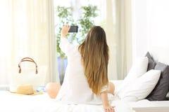 Mujer que toma el selfie en una habitación el vacaciones Imagen de archivo libre de regalías