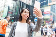 Mujer que toma el selfie por el teléfono móvil en Hong Kong Foto de archivo libre de regalías