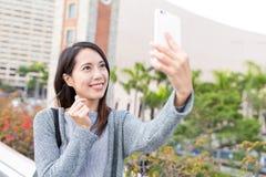 Mujer que toma el selfie por el teléfono móvil en Hong Kong Imagen de archivo libre de regalías