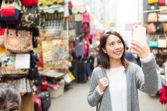 Mujer que toma el selfie por el teléfono móvil en la calle Foto de archivo