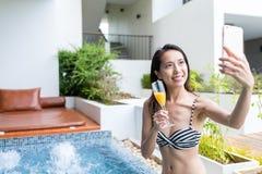 Mujer que toma el selfie por el teléfono móvil en piscina del Jacuzzi Foto de archivo
