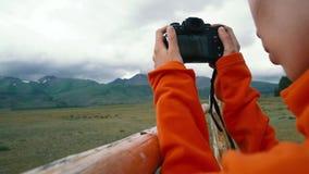Mujer que toma el smartphone de la fotografía que comparte la foto del fondo de la naturaleza del paisaje que disfruta de viaje d metrajes