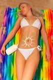 Mujer que toma el sol con dimensión de una variable del sol de la crema del bronceado Imagenes de archivo