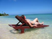 Mujer que toma el sol en una silla de la teca Fotografía de archivo libre de regalías