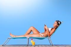 Mujer que toma el sol y que lee sus mensajes de texto Fotos de archivo libres de regalías