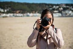 Mujer que toma a foto vista delantera con la cámara de DSLR fotos de archivo