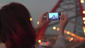 Mujer que toma imágenes de la ciudad con su smartphone en la puesta del sol metrajes