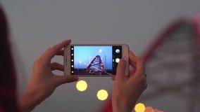 Mujer que toma imágenes de la ciudad con su smartphone en la puesta del sol almacen de video
