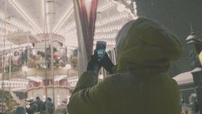 Mujer que toma imágenes de la escena europea del carrusel en Smartphone 4K Muchacha que disfruta de la estación de vacaciones de  almacen de video