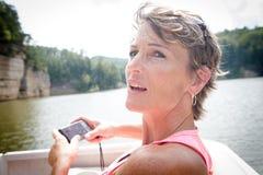 Mujer que toma imágenes de la vista escénica del agua Foto de archivo libre de regalías