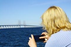 Mujer que toma imágenes en el puente de Oresund foto de archivo