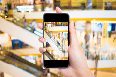 Mujer que toma imágenes en un teléfono móvil en la alameda de compras Imagen de archivo libre de regalías