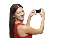 Mujer que toma imágenes a través del teléfono celular Imagen de archivo