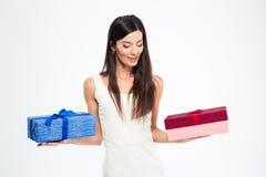 Mujer que toma la decisión entre dos cajas de regalo Foto de archivo