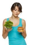 Mujer que toma la decisión entre la ensalada sana y los alimentos de preparación rápida Imagenes de archivo