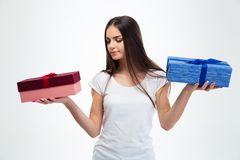 Mujer que toma la decisión entre dos cajas de regalo Fotografía de archivo libre de regalías