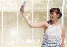 Mujer que toma la foto casual del selfie delante del invernadero Foto de archivo libre de regalías