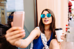 Mujer que toma la foto con café para llevar en su teléfono Imagen de archivo libre de regalías