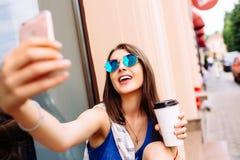 Mujer que toma la foto con café para llevar en su teléfono Fotografía de archivo libre de regalías
