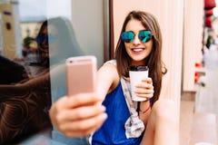 Mujer que toma la foto con café para llevar en su teléfono Imagen de archivo