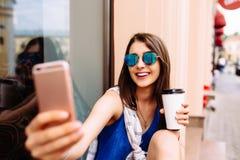 Mujer que toma la foto con café para llevar en su teléfono Fotos de archivo