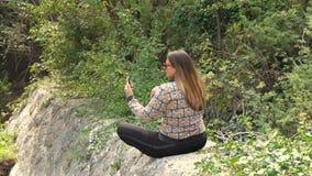 Mujer que toma la foto con el teléfono móvil